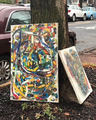 Image of two discarded paintings leaning against a tree on a city sidewalk