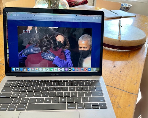 Image of computer screen showing Michelle Obama giving a hug to Kamala Harris at Inauguration Ceremony