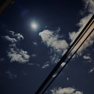 Photo of bright night sky with full moon, clouds, and telephone wires