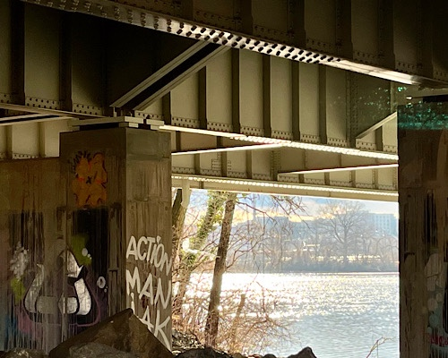 """Below underpass with view of river and graffiti that says """"action man"""""""