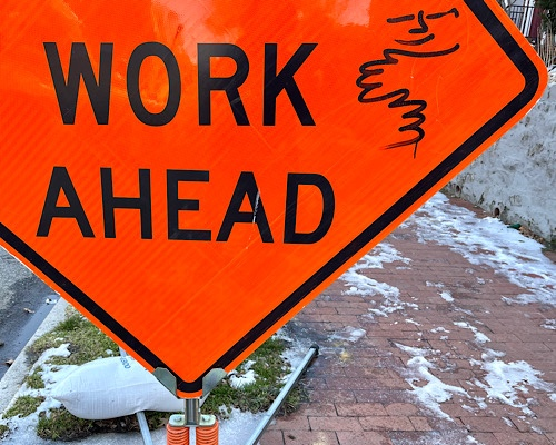 """Road sign that says """"road work ahead"""" with graffiti of a hug"""