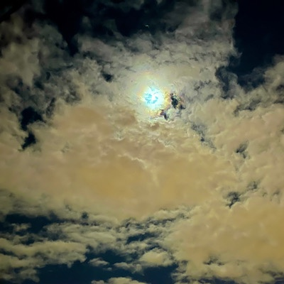 Full moon showing through clouds on night sky