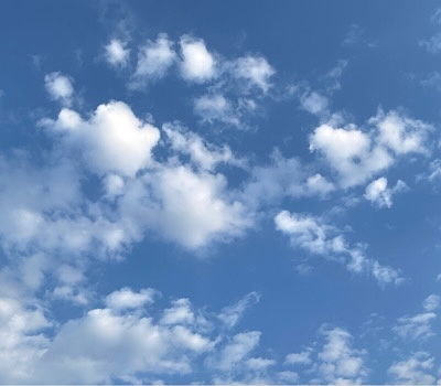 Fluffy white clouds, a couple heart-shaped, against a blue sky