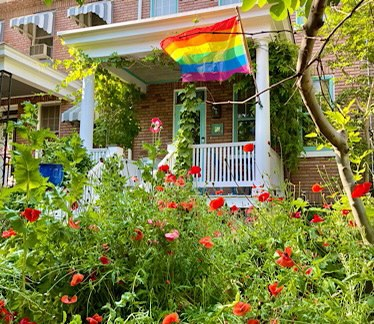 Photo of row house with poppies in the garden and a rainbow pride flag