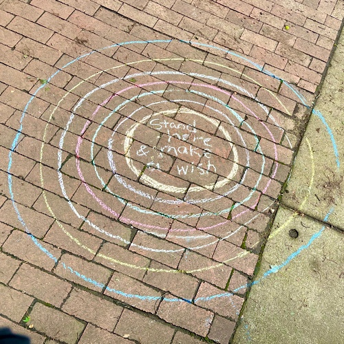 """Photo of chalk drawing of concentric circles around the words, """"stand here and make a wish."""""""