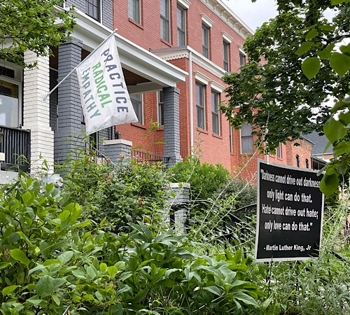 """Image of row house with flag that reads """"practice radical empathy"""""""