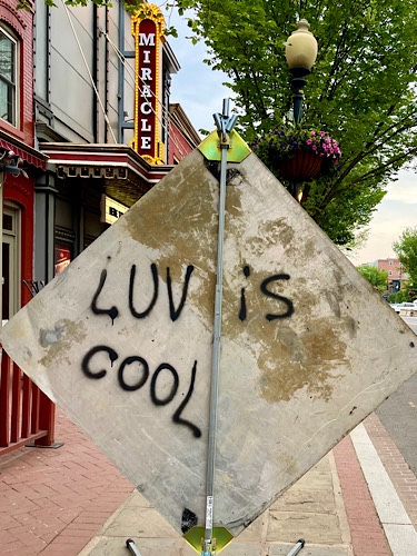 """Graffiti that says """"luv is cool"""" on back of street construction sign in front of marquee that says """"miracle"""""""