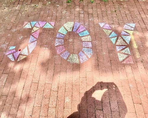 """Chalk drawing of word """"joy"""" on brick sidewalk"""