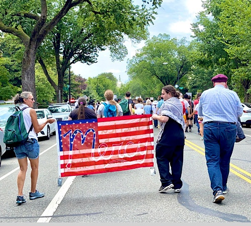 """Photo of people marching to the United States Capitol holding a banner like an US Flag with the word """"mercy"""" written on it."""