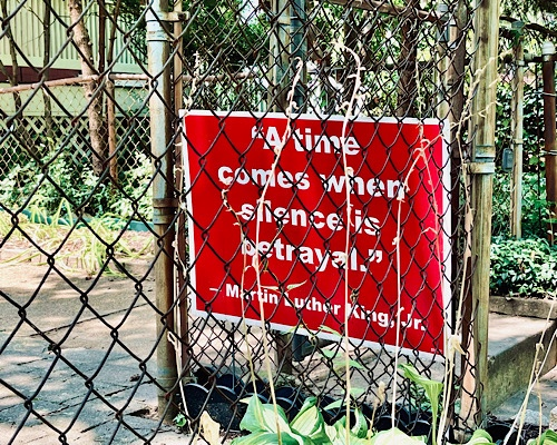 """Yard sign behind chain link fence has MLK Jr quote:  """"a time comes when silence is a  betrayal"""""""