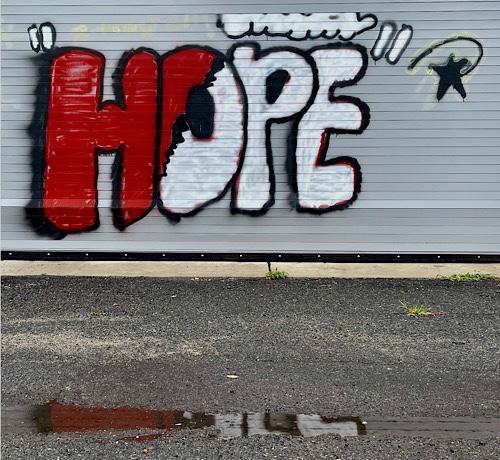 "Graffiti on a closed garage door reads:  ""HOPE"""