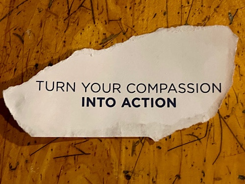 Piece of paper reads: turn your compassion into action